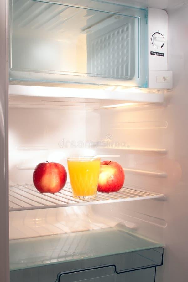 Pommes et jus dans le réfrigérateur vide   photographie stock libre de droits