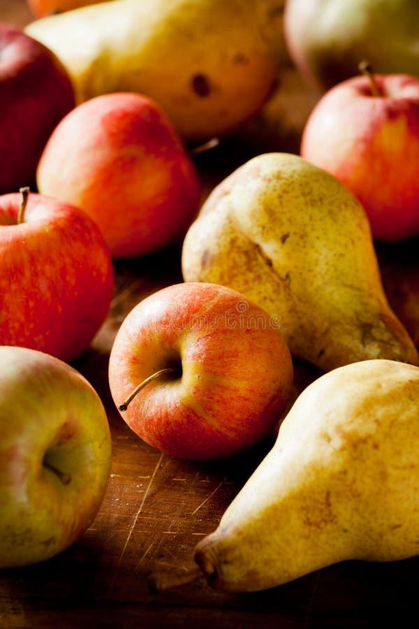 Pommes et poires organiques sur un Tableau en bois images stock