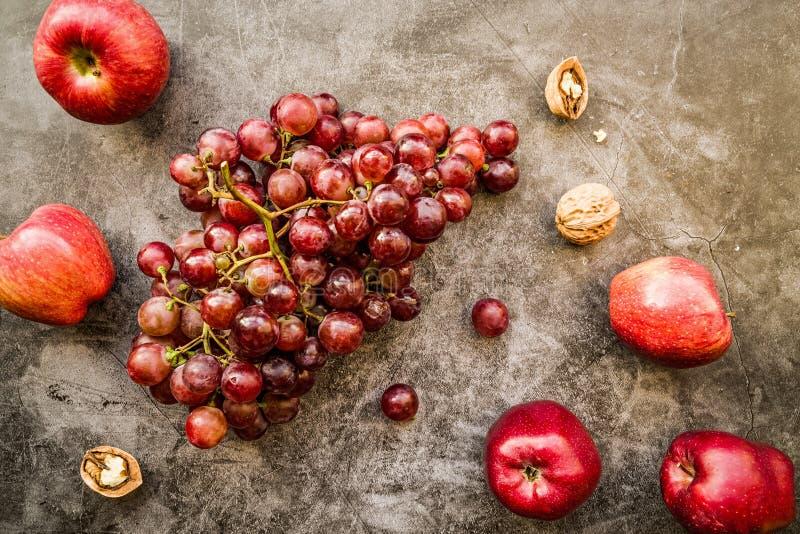 Pommes et raisins pourpres et rouges de fruit sur la vue supérieure de fond foncé image stock