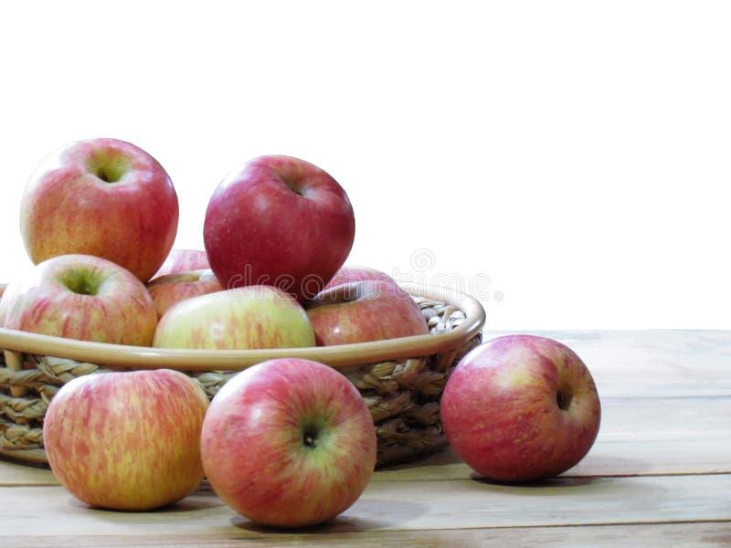 Pommes fra?ches organiques dans le panier sur la table en bois d'isolement sur le fond blanc images stock