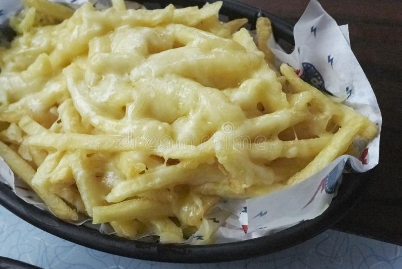 Pommes frites avec du fromage fondu image libre de droits