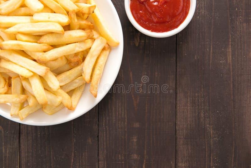 Pommes frites avec le ketchup sur le fond en bois photographie stock