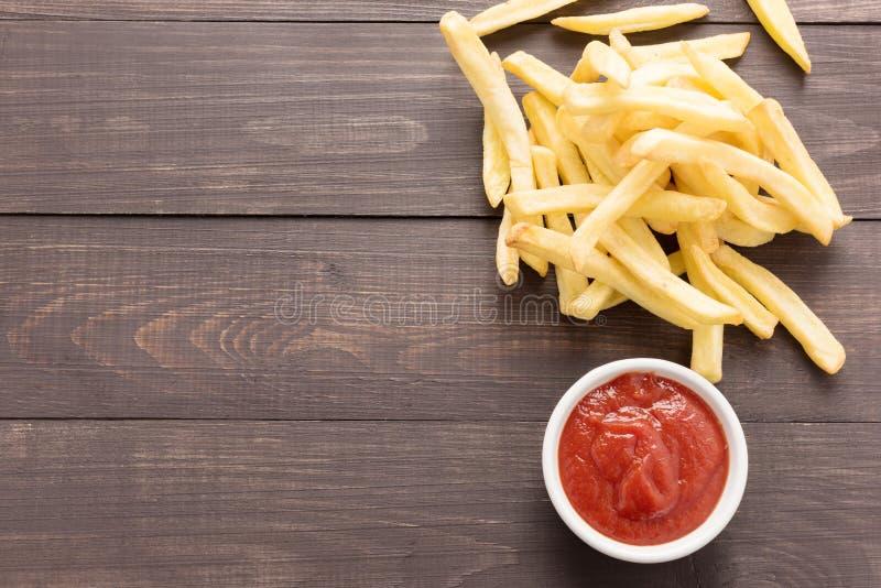 Pommes frites avec le ketchup sur le fond en bois photo stock