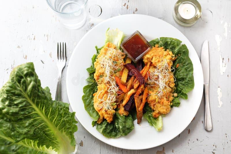 Pommes frites cuites au four colorées avec des légumes avec le ragoût végétal sur la salade 'Iceberg' image libre de droits
