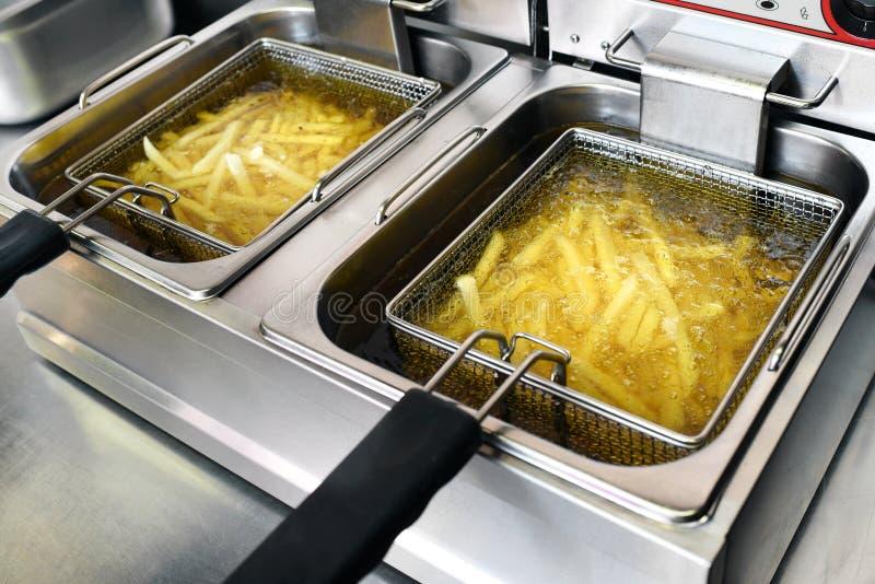 Pommes frites eller potatischiper som steker i olja royaltyfri fotografi