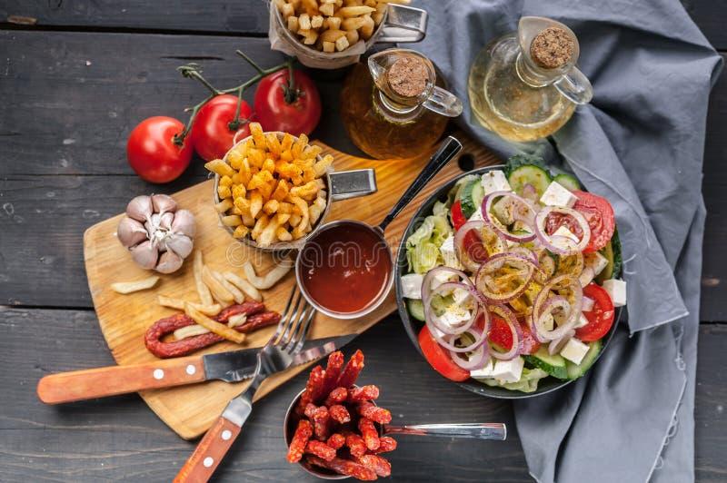 Pommes frites faites maison et salade grecque Oignons, ail, sauce de saucisse et tomate fumée, fourchette et cuillère sur une tab image libre de droits