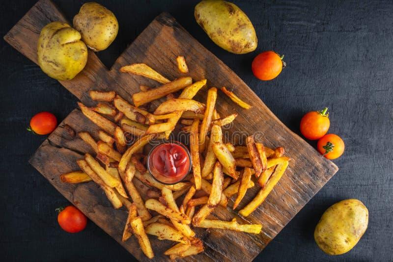 Pommes frites fraîches avec le ketchup sur le fond en bois image stock