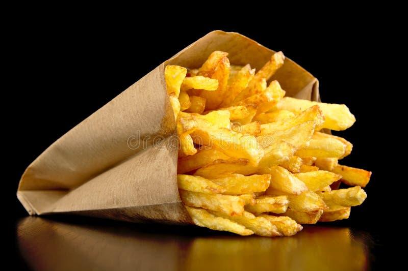 Pommes frites i den pappers- påsen som isoleras på svart arkivfoton
