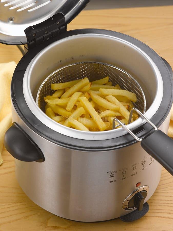 Pommes frites in i en djup stekpanna för hem royaltyfri bild