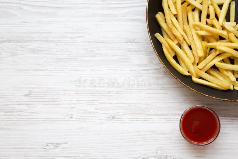 Pommes frites i en stekpanna med ketchup på en vit trätabell, bästa sikt arkivbilder