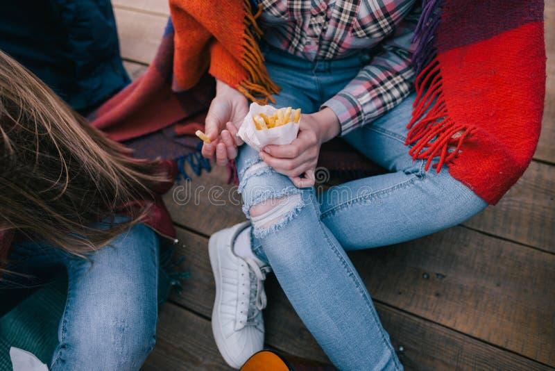 Pommes frites i händer av den stilfulla unga flickan royaltyfri bild