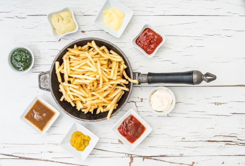 Pommes frites i stekpanna med bästa sikt för såser arkivfoto