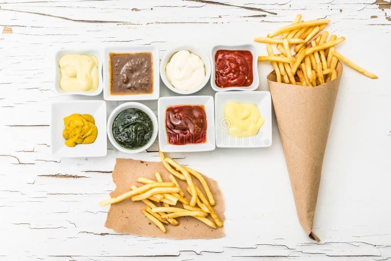 Pommes frites med olika såser fotografering för bildbyråer