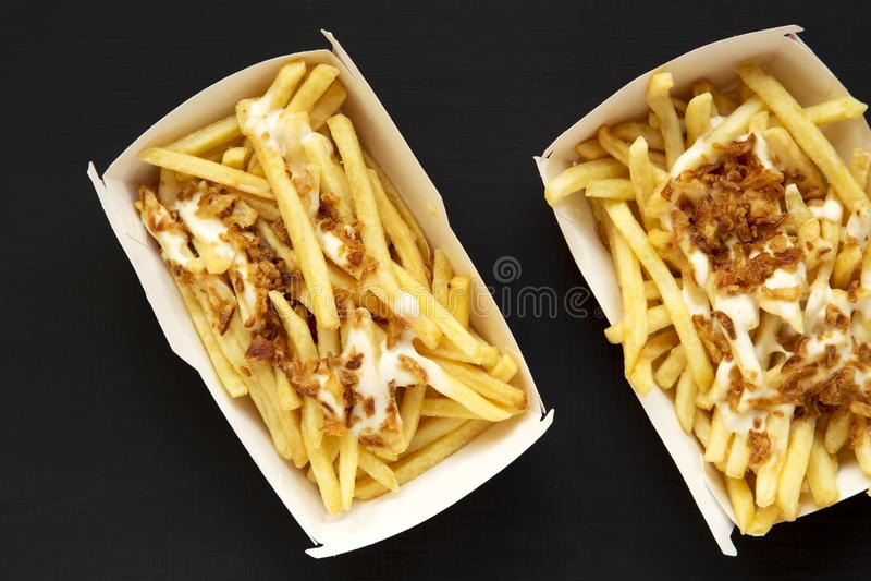 Pommes-Frites mit Käsesoße und gebratener Zwiebel in den Papierkästen auf einem schwarzen Hintergrund, Draufsicht Flache Lage, vo lizenzfreie stockfotos