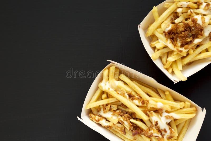 Pommes-Frites mit Käsesoße und gebratener Zwiebel in den Papierkästen auf einer schwarzen Oberfläche, Draufsicht Flache Lage, von stockbilder
