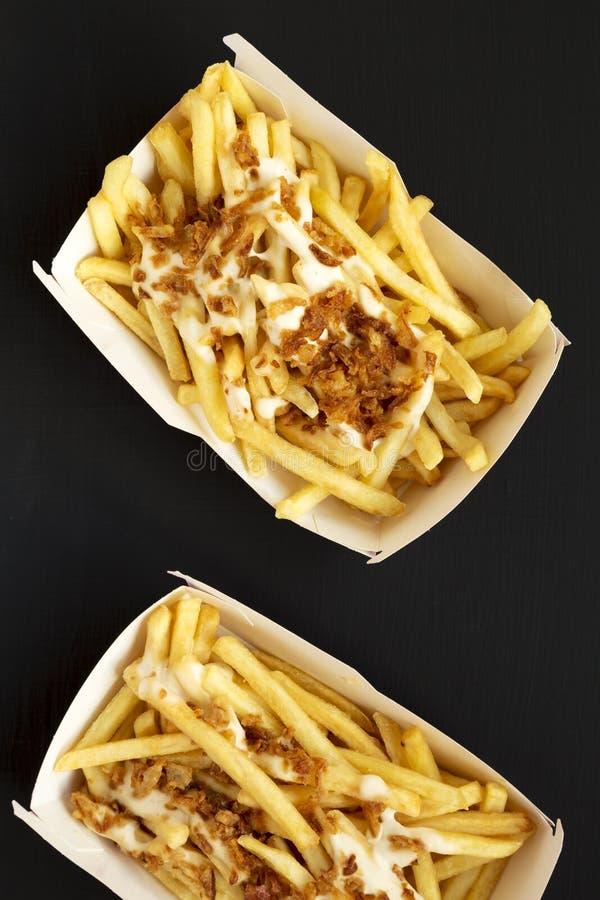 Pommes-Frites mit Käsesoße und gebratener Zwiebel in den Papierkästen auf einer schwarzen Oberfläche, Draufsicht Flache Lage, von stockfotos