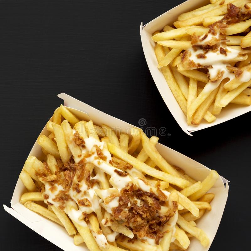 Pommes-Frites mit Käsesoße und Zwiebel in einem Papierkasten auf einem schwarzen Hintergrund, Draufsicht Flache Lage, von oben, o stockbild