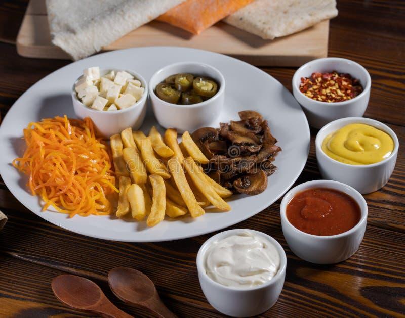 Pommes frites morötter, gurkor tjänade som på en tabell med olika såser royaltyfri fotografi