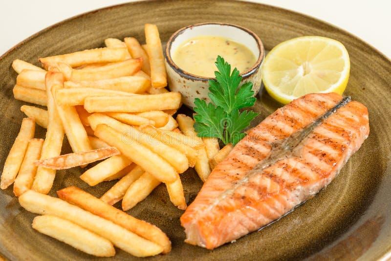 Pommes frites och ett stycke av den röda stekte fisklaxen med en persilja spricker ut med sås på en stor platta arkivfoton