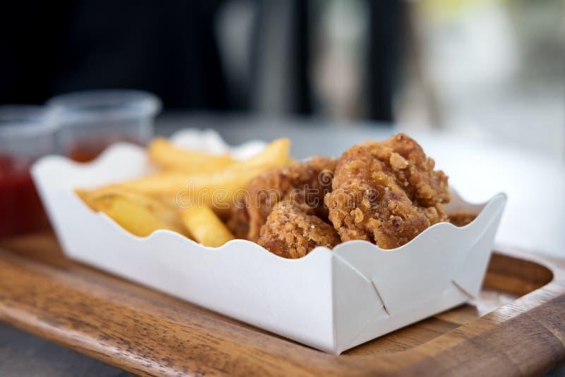 Pommes frites och stekt kyckling i vitbokplatta med ketchup och chilisås i plast- koppar royaltyfri foto