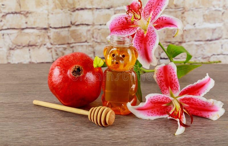 Pommes, grenades et miel sur un plat de vintage dans la cuisine Table en bois L'arrangement traditionnel pendant la nouvelle anné photo stock