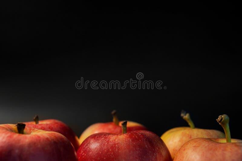 Pommes juteuses rouges Pommes rouges mûres sur le fond noir Les belles pommes sont forme idéale Vue supérieure avec l'espace pour image libre de droits