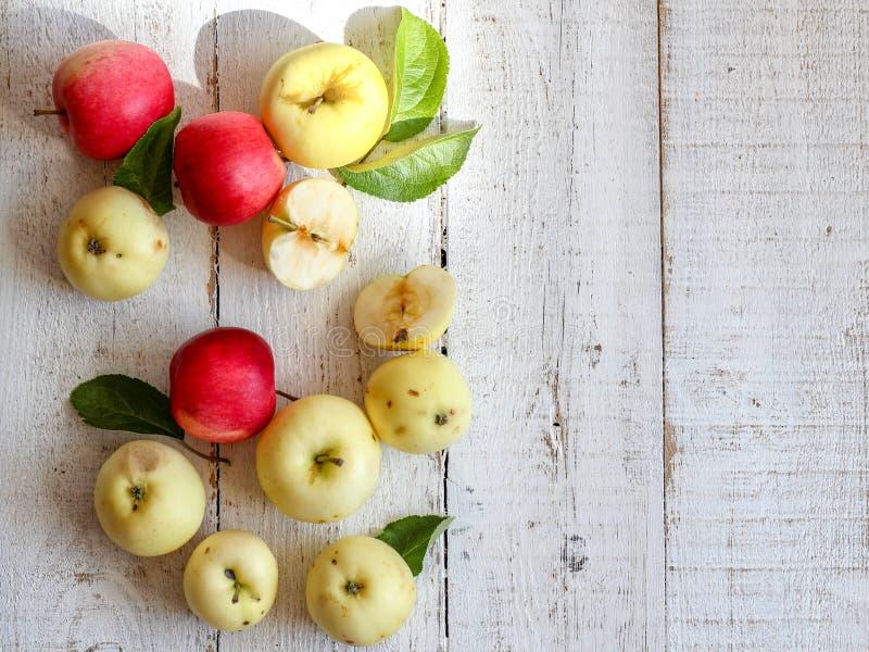 Pommes organiques vertes et rouges sur une table en bois blanche photographie stock libre de droits