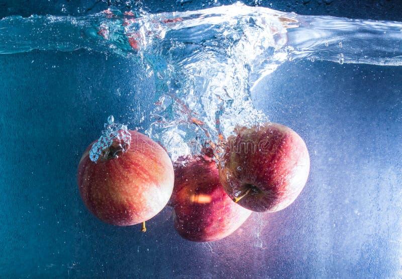 pommes Rouge-jaunes tombant dans l'eau claire photo libre de droits