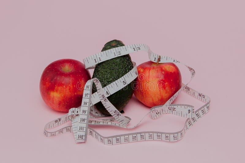 Pommes rouges avec un critère avec l'avocat sur le fond rose Concept de nourriture de régime Ingrédient de nourriture de régime images stock