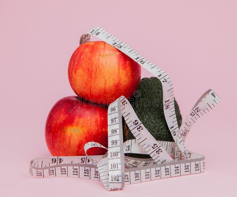 Pommes rouges avec un critère avec l'avocat sur le fond rose Concept de nourriture de régime Ingrédient de nourriture de régime photos libres de droits