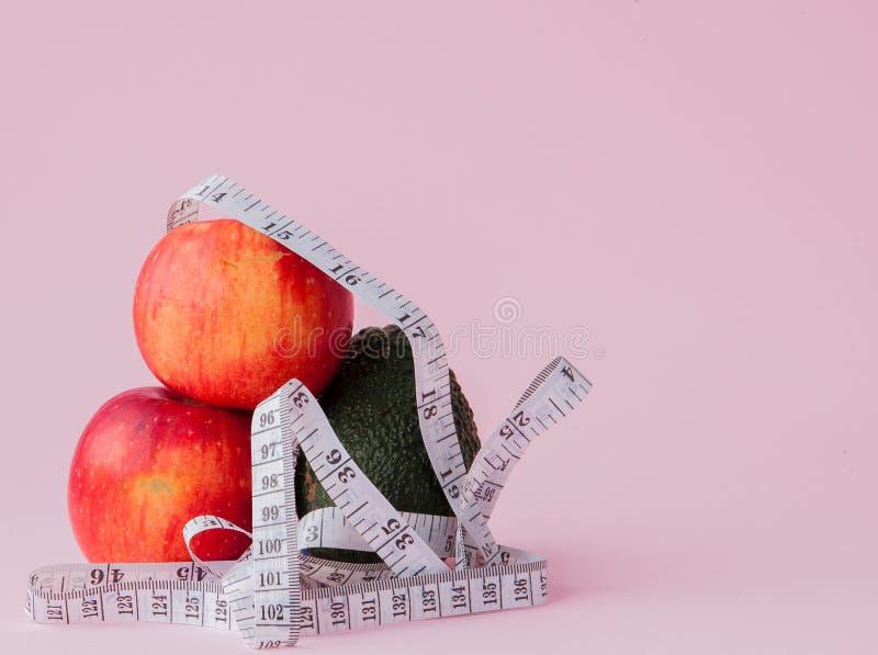 Pommes rouges avec un critère avec l'avocat sur le fond rose Concept de nourriture de régime Ingrédient de nourriture de régime photo stock