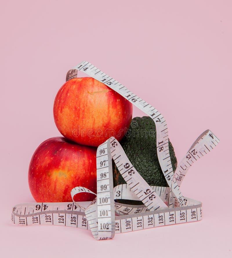 Pommes rouges avec un critère avec l'avocat sur le fond rose Concept de nourriture de régime Ingrédient de nourriture de régime images libres de droits