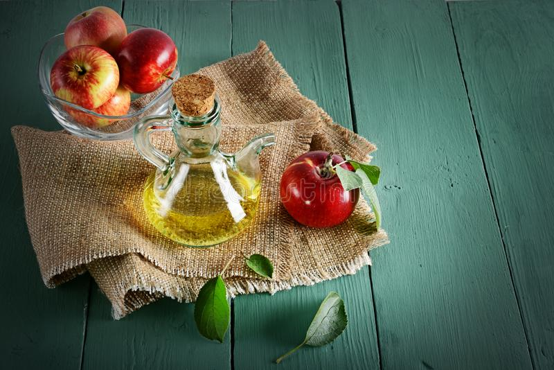 Pommes rouges en vinaigre de vase et de cidre de pomme sur la table en bois Concentré photos stock