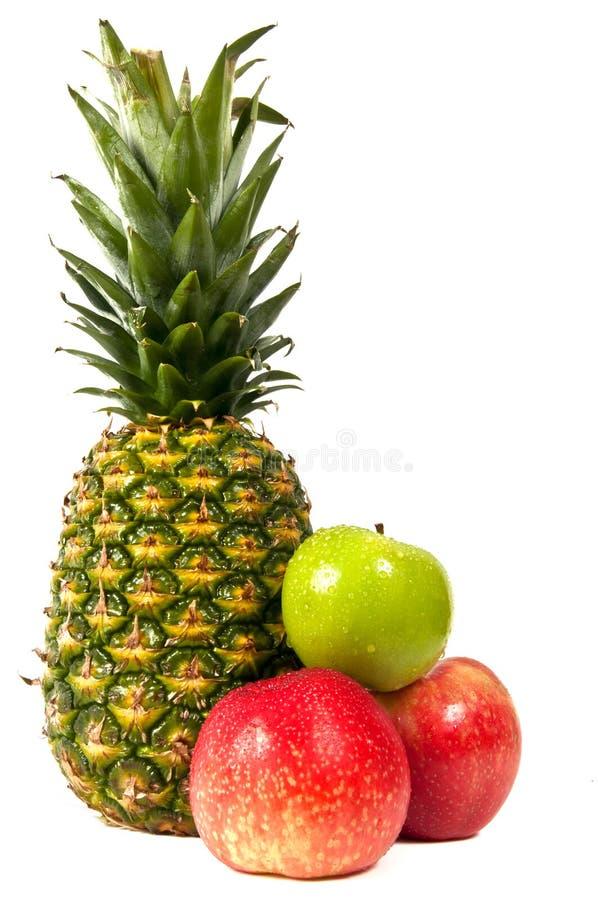 Pommes rouges et vertes avec un ananas entier. image libre de droits