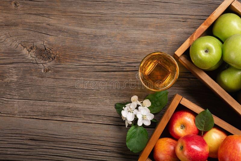 Pommes rouges et vertes mûres dans la boîte en bois avec la branche des fleurs blanches et du verre de jus frais sur une table en photo libre de droits