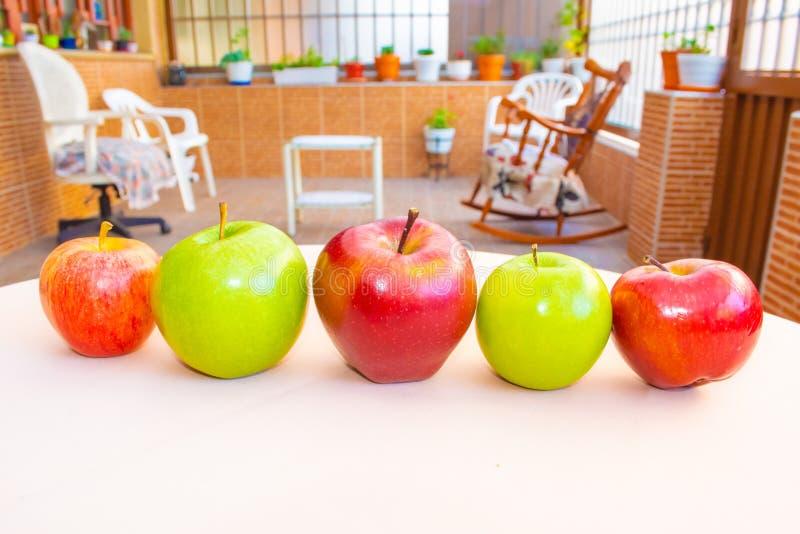 Pommes rouges et vertes sur la table de jardin photographie stock libre de droits