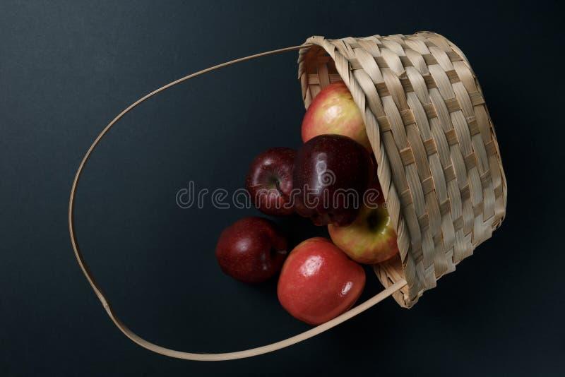 Pommes rouges m?res dans un panier sur un fond fonc? images stock