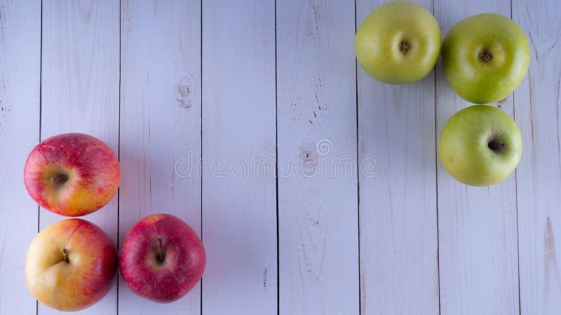 Pommes sur une table en bois blanche Récolte des pommes vertes et rouges image libre de droits