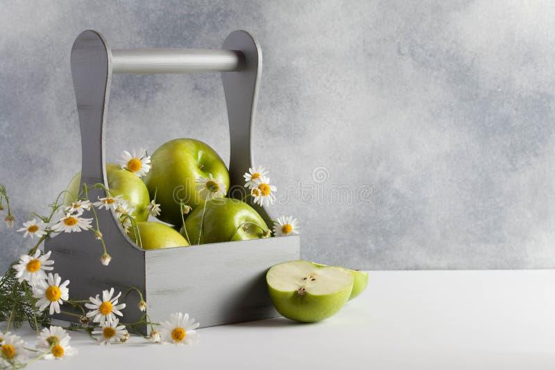 Pommes vertes avec la camomille images stock