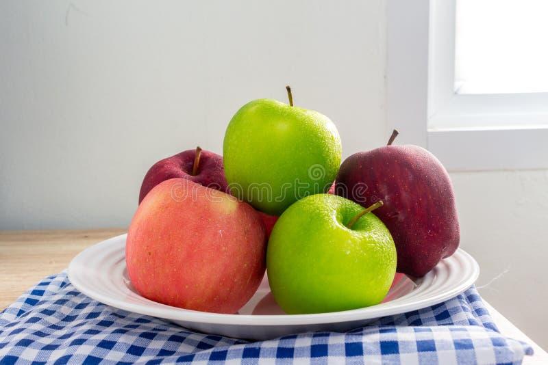 Pommes vertes et rouges mûres sur le fond blanc de table photographie stock