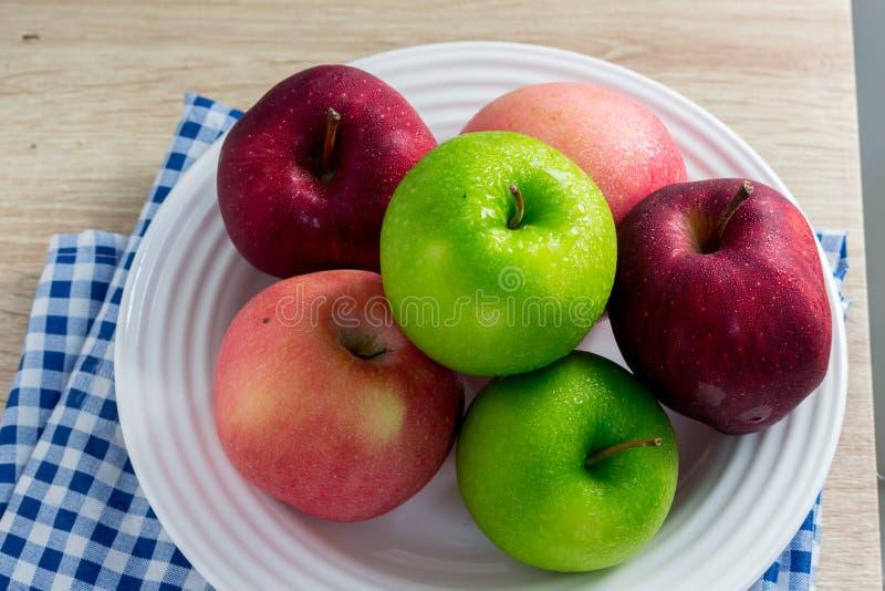 Pommes vertes et rouges mûres sur le fond blanc de table photo libre de droits