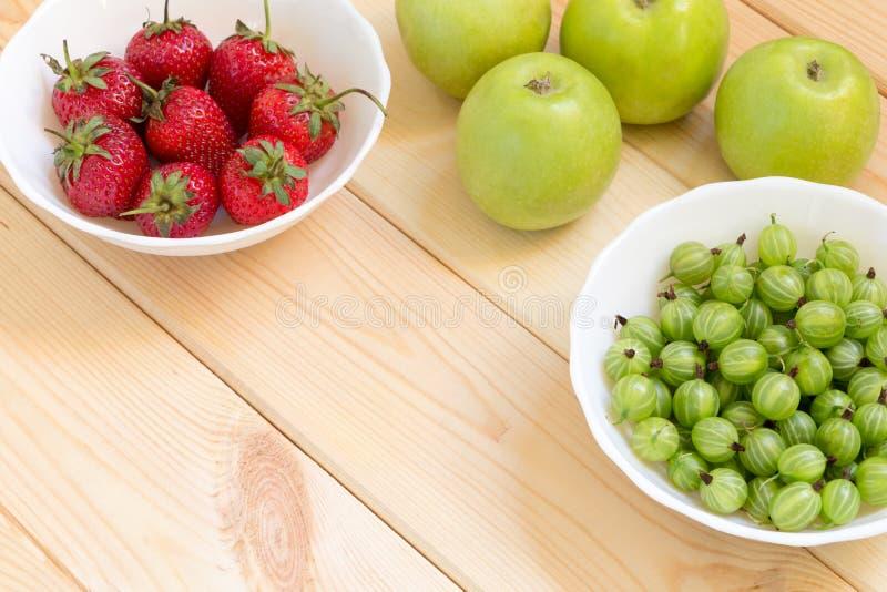 Pommes vertes, groseille à maquereau et fraises rouges dans les bowles blancs sur la table en bois légère images stock