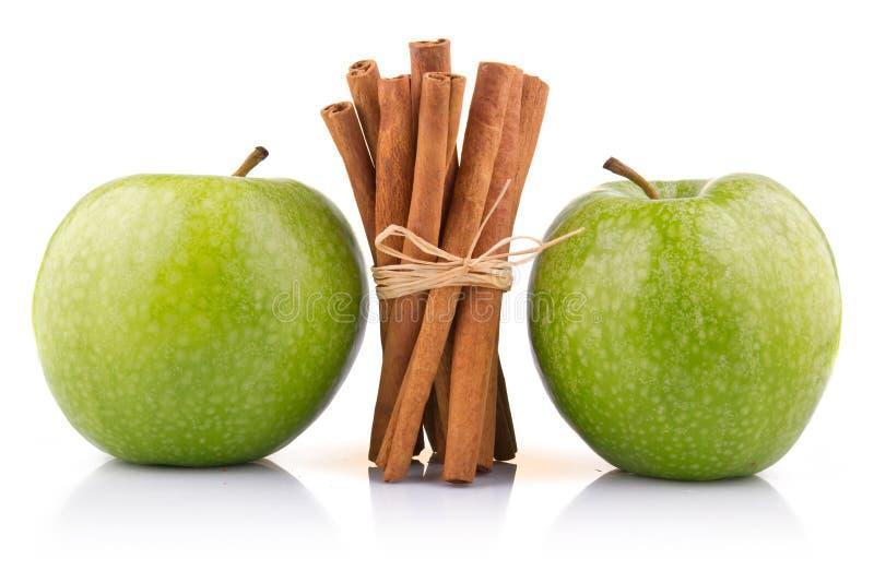 Pommes vertes mûres avec des bâtons de cannelle d'isolement images stock