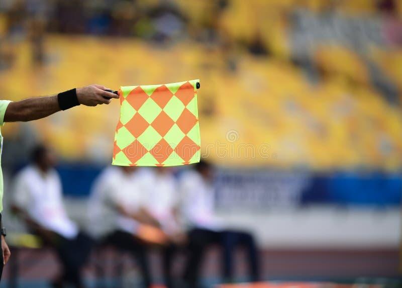 Pomocnicza arbitra chwyta flaga, offside sygnał zdjęcia royalty free