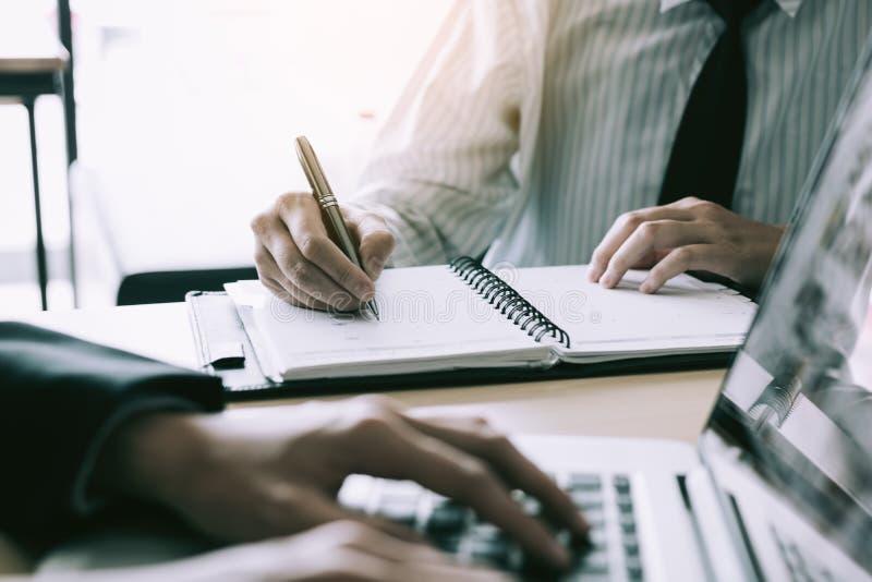 Pomocniczy kierownik bierze notatki nadzorca który używa laptop dla pracy zdjęcia stock