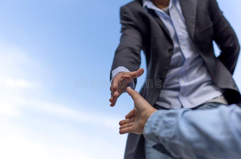Pomocy pojęcia ręka dosięga out pomagać someone z niebieskim niebem obraz stock