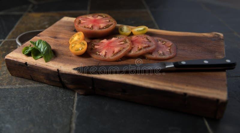 Pomodori affettati di cimelio sul tagliere con il coltello dal lato immagine stock libera da diritti