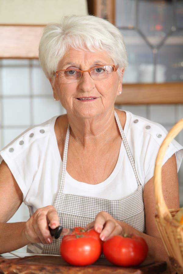 Pomodori anziani di taglio della donna immagine stock