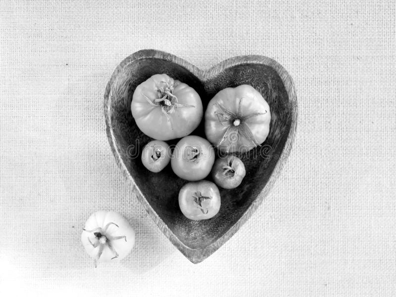 Pomodori in bianco e nero in ciotola a forma di del cuore fotografia stock libera da diritti