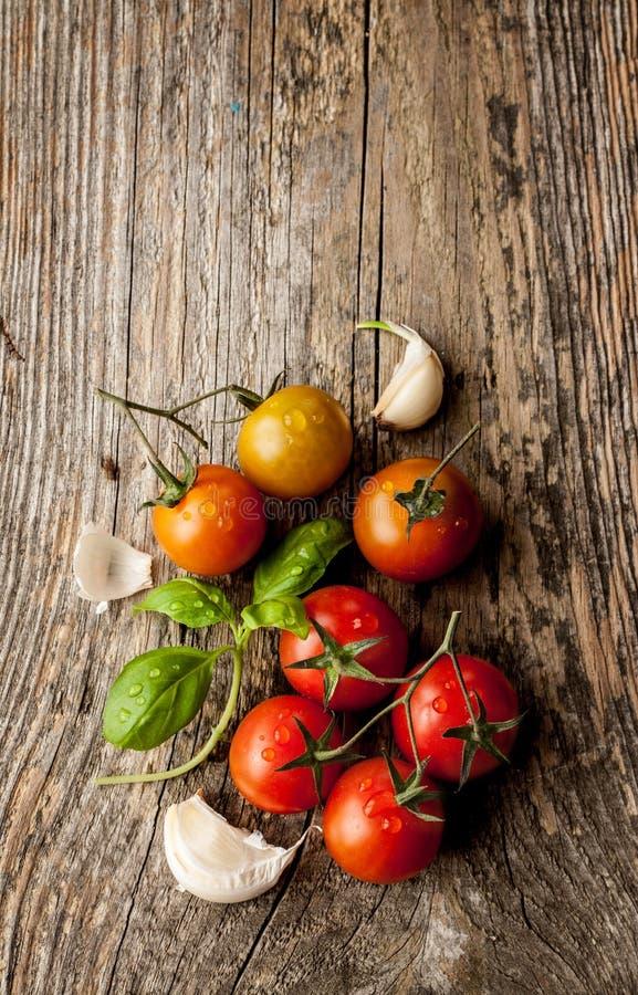 Pomodori ciliegia, aglio e basilico fresco sulla tavola di legno d'annata immagine stock